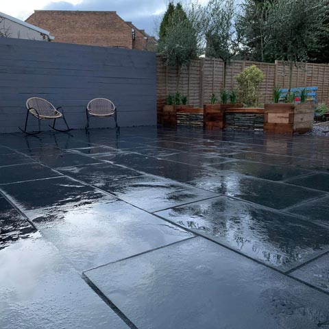 Black Limestone paving with raised borders in slate and softwood sleepers in Teddington