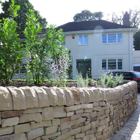 Beautiful stone wall with bedding and block paved driveway in Esher