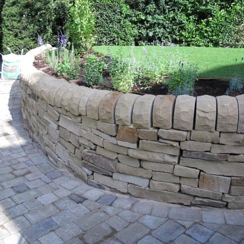Beautiful stone wall with bedding and block paved driveway in Kingston-upon-Thames