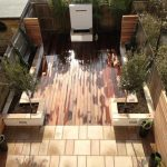 Hardwood decking with stone planters in Raynes Park