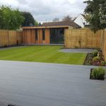 Grey composite decking with lawn and planting in Kingston