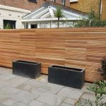 Raised rendered seating area with bespoke storage and Cedar fences in Teddington